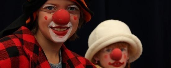 Zwei Circuskinder als Clowns mit roten Nasen